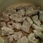 Coat the meat with the flour mixture.  Brown the meat on all sides in the oil on medium heat.